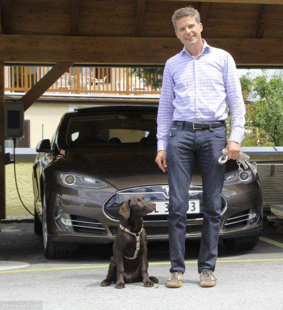 Richard Absenger mit Hündin Luna vor braunem Tesla S eines Norwegers.